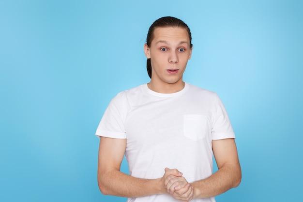 Zdenerwowany młody facet w koszulce na białym tle na niebieskim tle. ludzkie emocje, mimika twarzy
