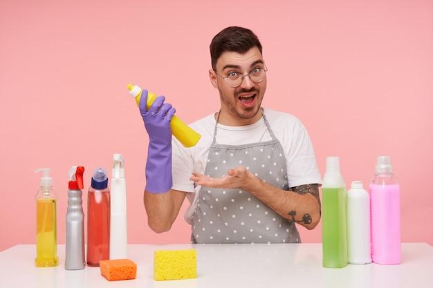 Zdenerwowany młody, ładny brązowowłosy mężczyzna z krótką fryzurą trzymający butelkę chemii gospodarczej w uniesionej dłoni i wyglądający podekscytowany, pozując na różu