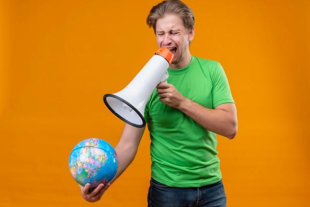 Zdenerwowany młody przystojny mężczyzna ubrany w zielony t-shirt trzymając kulę ziemską krzycząc do megafonu stojącego nad pomarańczową ścianą