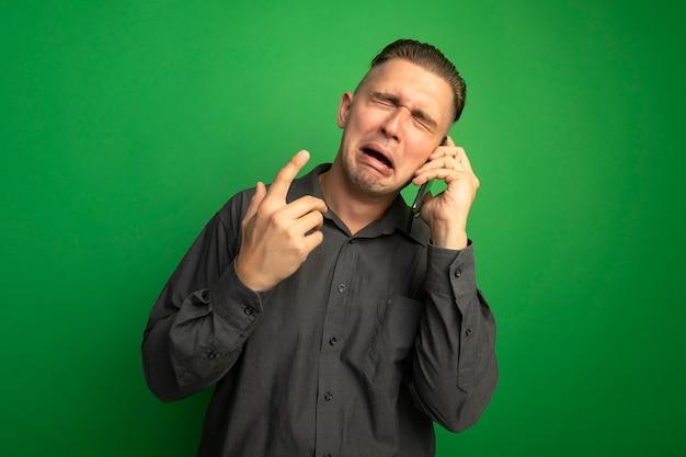 Zdenerwowany młody przystojny mężczyzna w szarej koszuli płacze podczas rozmowy na telefon komórkowy stojąc na zielonej ścianie