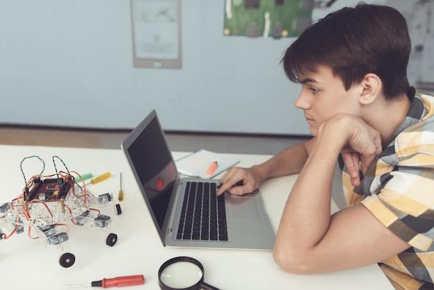 Zdenerwowany nastolatek w koszuli programowania robota w domu.