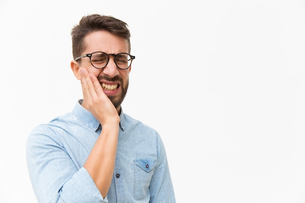 Zdenerwowany nieszczęśliwy facet trzyma policzek z bólem twarzy