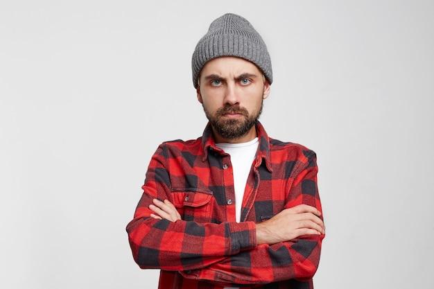 Zdenerwowany nieszczęśliwy młody człowiek na białej ścianie