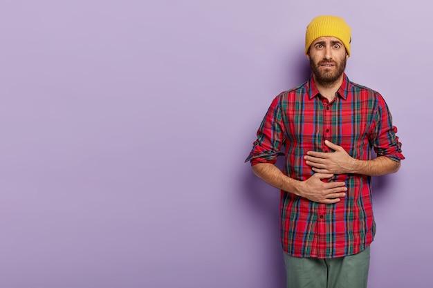 Zdenerwowany, niezadowolony młody człowiek dotyka brzucha