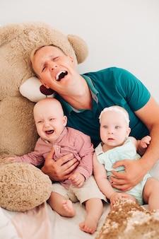 Zdenerwowany ojciec siedzi w pokoju z jednym płaczącym małym dzieckiem i innym spokojnym noworodkiem w domu. koncepcja rodziny i rodzicielstwa