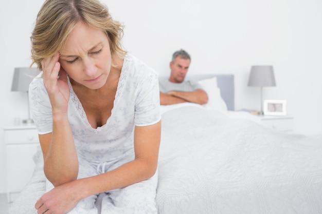 Zdenerwowany para siedzi na przeciwnych końcach łóżka po walce