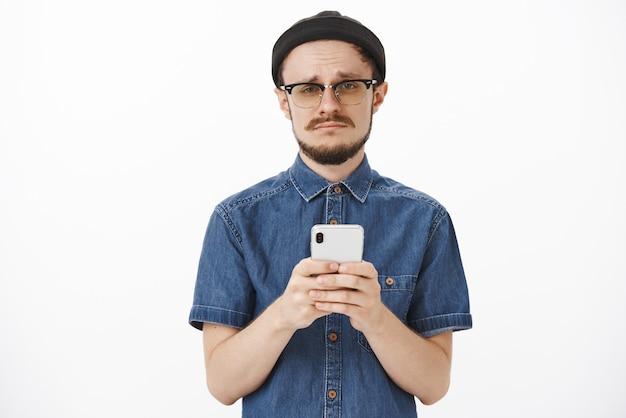 Zdenerwowany ponury uroczy brodaty facet w czarnej czapce i okularach robi smutną minę i marszczy brwi, trzymając smartfon wyrażający zazdrość lub żal, tracąc szansę na zakup biletów online