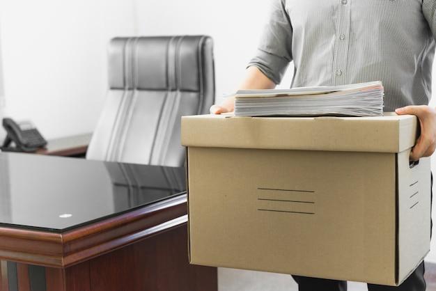 Zdenerwowany pracownik pakuje rzeczy w pudełku