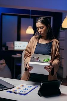 Zdenerwowany pracownik zwolniony z pracy pakujący rzeczy osobiste. smutna kobieta trzyma swoje rzeczy późno w nocy w biurze po zwolnieniu z pracy. zwolniona bizneswoman, kryzys gospodarczy