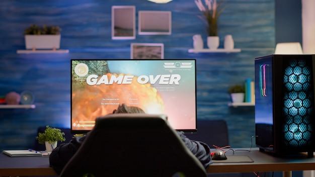 Zdenerwowany profesjonalny gracz kobieta nosi zestaw słuchawkowy, przegrywając kosmiczną strzelankę w rywalizacji cybersportowej. zmęczony profesjonalny gracz cybernetyczny grający w gry wideo online na potężnym komputerze osobistym ze światłami rgb.