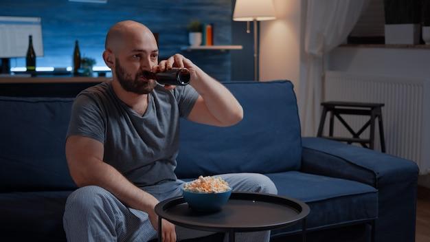 Zdenerwowany profesjonalny gracz siedzący przed telewizorem, przegrywający piłkarskie gry wideo