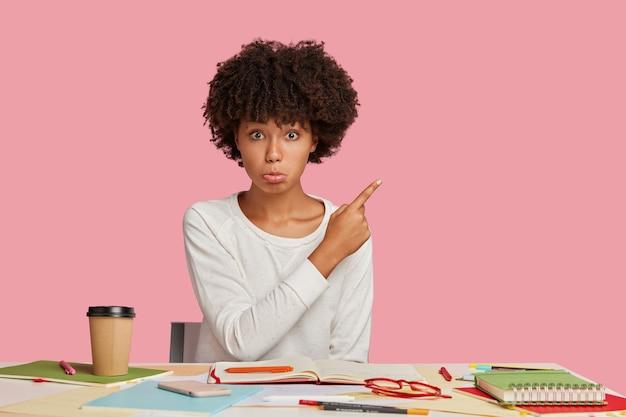 Zdenerwowany projektant marszczy usta z niezadowoleniem, siedzi przy biurku, pije napój z jednorazowego kubka, wskazuje na miejsce na kopię