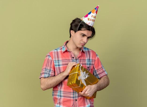 Zdenerwowany przystojny kaukaski mężczyzna w czapce urodzinowej trzyma pudełko na prezent