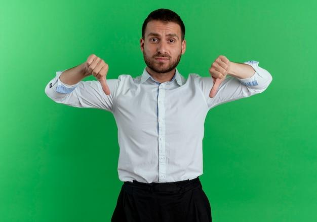 Zdenerwowany przystojny mężczyzna kciuki w dół dwiema rękami na białym tle na zielonej ścianie
