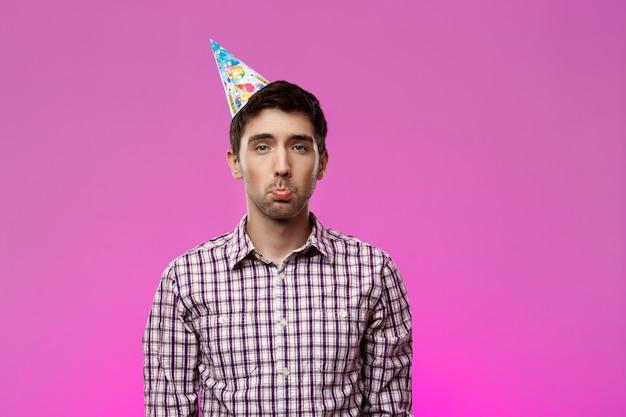 Zdenerwowany przystojny mężczyzna na fioletowe ściany. przyjęcie urodzinowe.
