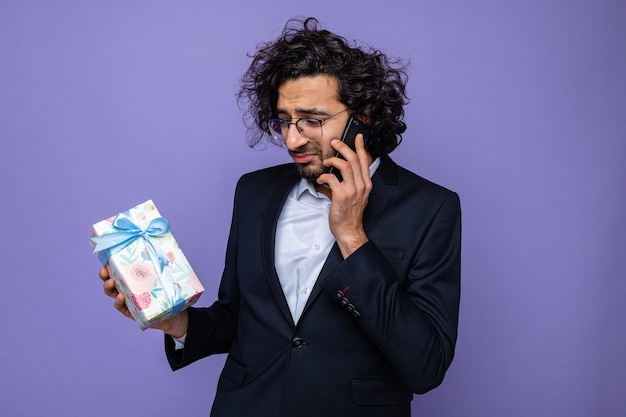 Zdenerwowany przystojny mężczyzna w garniturze trzyma prezent rozmawia przez telefon komórkowy ze smutnym wyrazem z okazji międzynarodowego dnia kobiet 8 marca stojąc na fioletowym tle