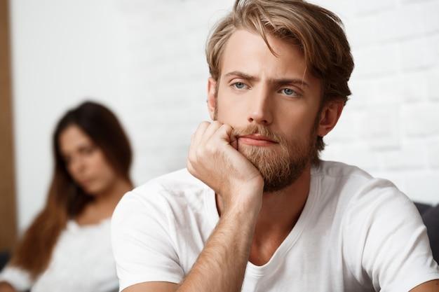 Zdenerwowany przystojny mężczyzna w kłótni ze swoją dziewczyną