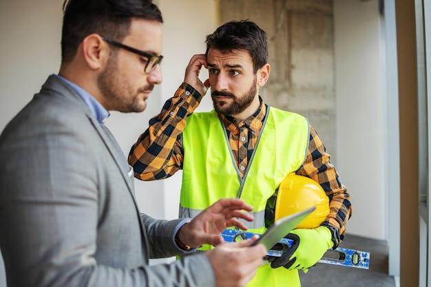Zdenerwowany robotnik budowlany patrząc na swojego przełożonego i zdezorientowany, co jest nie tak