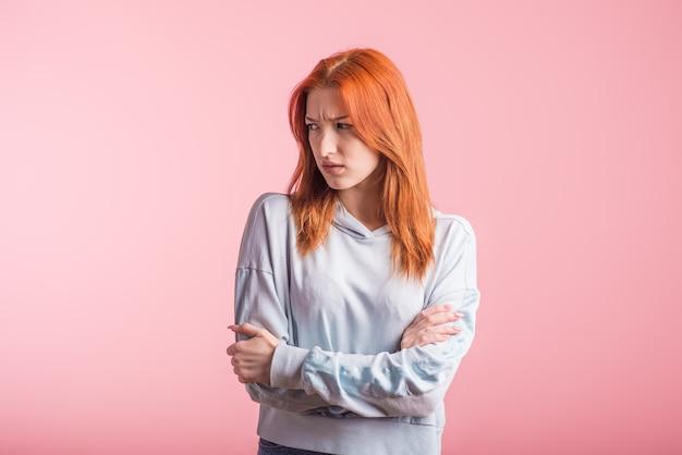 Zdenerwowany rudy dziewczyna ze skrzyżowanymi rękami w studio na różowym tle