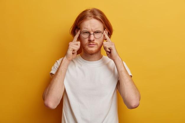 Zdenerwowany rudy mężczyzna przyciska palce do skroni, ma bezradny wyraz twarzy