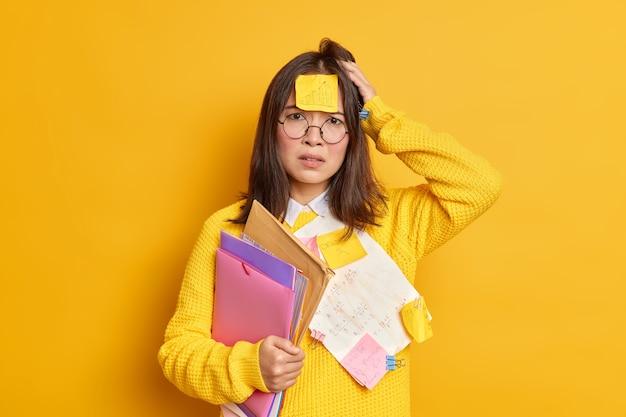 Zdenerwowany sfrustrowany pracownik biurowy zdziwiony, że ma dużo pracy, ma naklejkę na czole, stara się zrobić wszystko na czas, trzyma teczki z papierami, nosi duże okrągłe okulary.