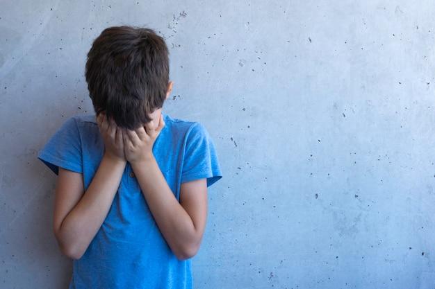 Zdenerwowany smutny chłopiec stojący samotnie i oparty na szarej ścianie