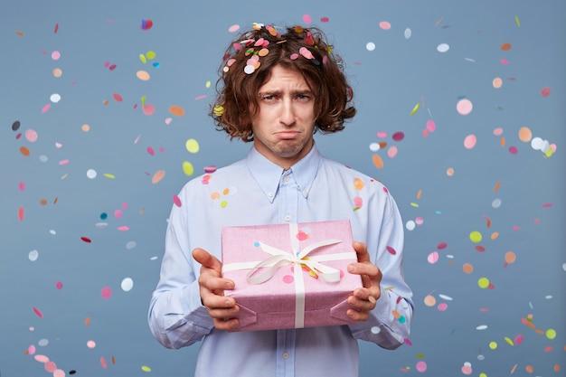 Zdenerwowany urażony facet z wydymaną dolną wargą, który trzyma różowe pudełko z białą wstążką