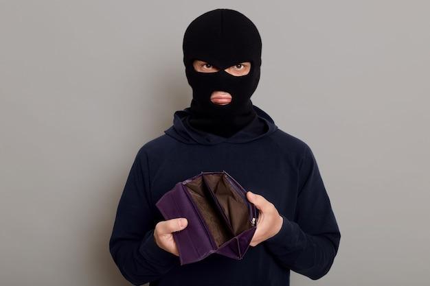 Zdenerwowany włamywacz ubrany w czarny golf i kominiarkę trzymający pusty portfel