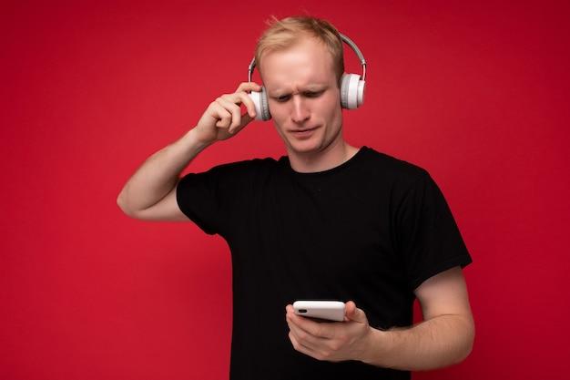 Zdenerwowany zamyślony przystojny blondyn młody człowiek ubrany w czarny t-shirt i stojąc białe słuchawki