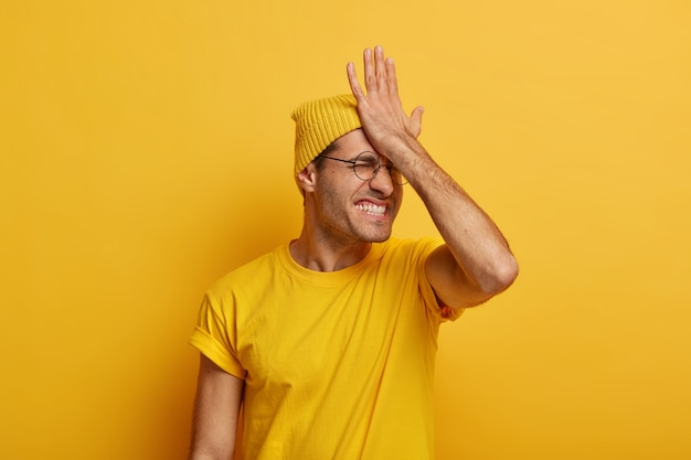 Zdenerwowany zestresowany mężczyzna trzyma dłoń na czole, ma złą pamięć, mruży twarz i zaciska zęby, nosi zwykłe ubranie, nie pamięta ważnej rzeczy