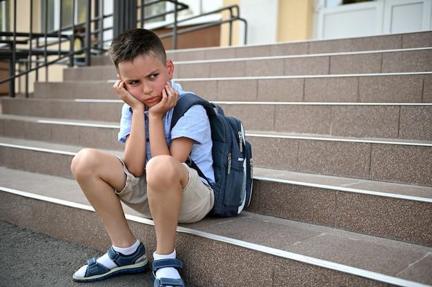 Zdenerwowany zmartwiony chłopiec z plecakiem siedzący na schodach przy szkole. zastraszanie, samotność, trudności w nauce. powrót do koncepcji szkoły