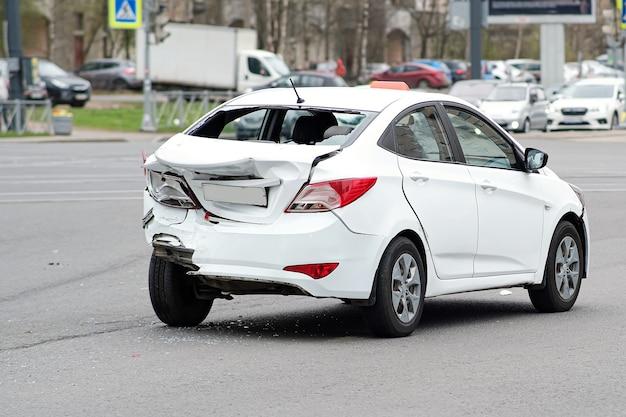 Zderzenie samochodów. biały samochód taksówki doznał poważnych uszkodzeń tylnej części nadwozia. zepsuty zderzak i pokrywa bagażnika.