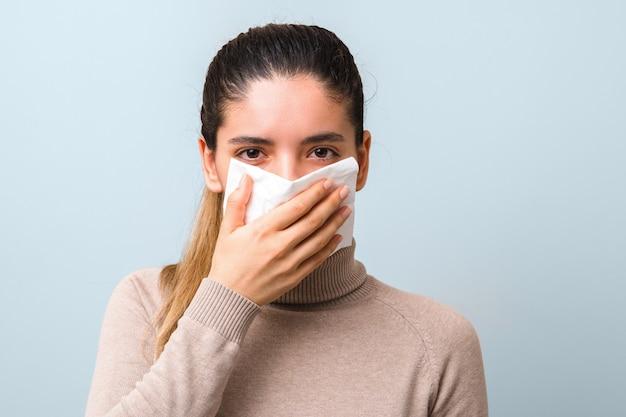 Zdesperowana kobieta z gorączką i bólem głowy, kichająca i kaszląca.