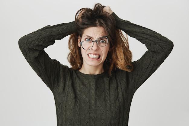 Zdesperowana szalona kobieta czochra włosy, nosi krzywe okulary, zaciska zęby w rozpaczy i złości