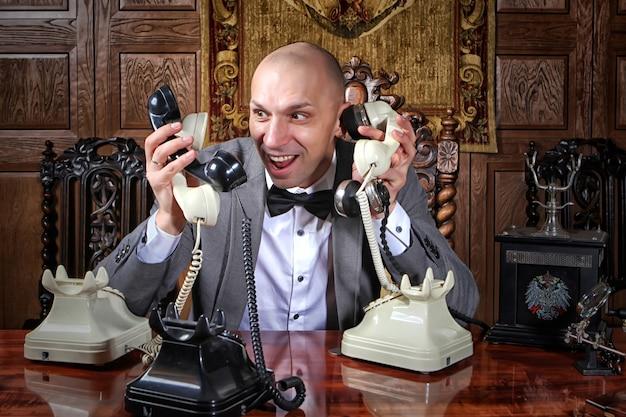 Zdesperowany biznesmen w szybkim tempie showman pracuje w biurze i dużo dzwoni, trzyma dużo słuchawek. koncepcja zarządzania przedsiębiorstwem. zestresowany mężczyzna rozmawia przez wiele telefonów jednocześnie. miejsce na napis lub logo