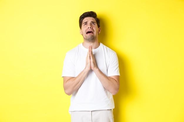 Zdesperowany mężczyzna błagający boga, trzymając się za ręce w modlitwie i patrząc w górę zmartwiony, stojący na żółtym tle. skopiuj miejsce