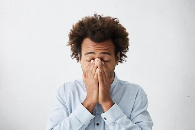 Zdesperowany mężczyzna o gęstych ciemnych włosach zakrywających twarz, zmęczony dłońmi zamykającymi oczy