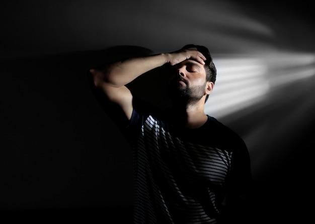 Zdesperowany mężczyzna z bliska portret z długim cieniem na czarnym tle lowkey