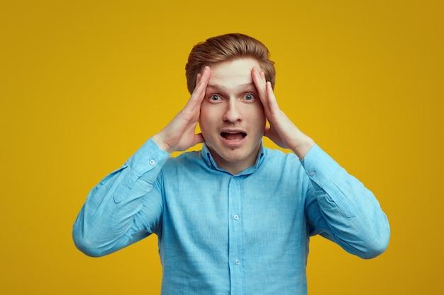 Zdesperowany młody mężczyzna ma ból głowy i zaczyna krzyczeć
