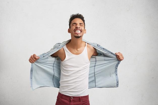 Zdesperowany młody stylowy mężczyzna rasy mieszanej z wąsami i brodą