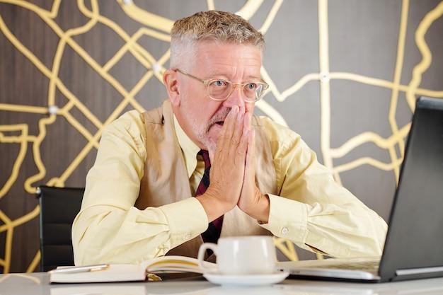 Zdesperowany starszy biznesmen zakrywający usta rękami podczas czytania szokujących wiadomości o kryzysie finansowym na swoim laptopie w kawiarni