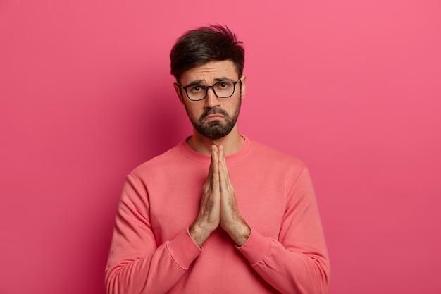 Zdesperowany winny, nieogolony mężczyzna pokazuje splecione dłonie, przeprasza za zły błąd, błaga o pomoc, wygląda nieszczęśliwie, nosi okulary i swobodny sweter, pozuje w domu na różowej ścianie.