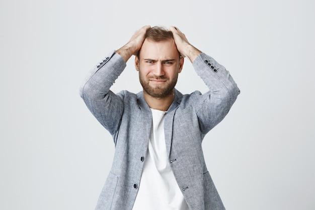 Zdesperowany zdenerwowany zdenerwowany mężczyzna chwycić głowę przeszkadza