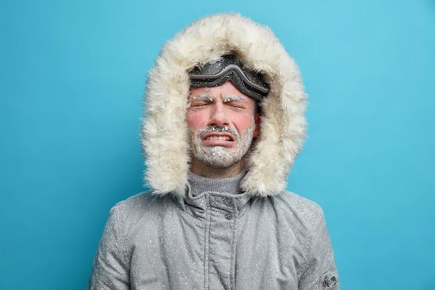 Zdesperowany zmarznięty zmarznięty mężczyzna płacze, gdy jest bardzo zimno podczas zamieci i silnej burzy śnieżnej ubrany w termo-szarą kurtkę z kapturem jedzie na nartach.