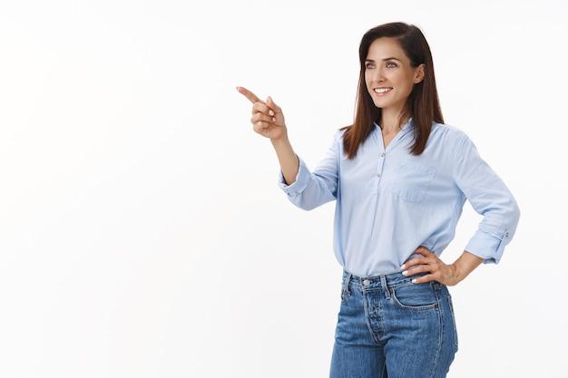Zdeterminowana bizneswoman czuje się zmotywowana, wygrywa transakcję, osiąga sukces, stoi na wpół obrócona wskazuje, wygląda na zadowoloną lewą przestrzeń, widzi dobrą ofertę, koncepcję biznesową, stoi pewnie biała ściana