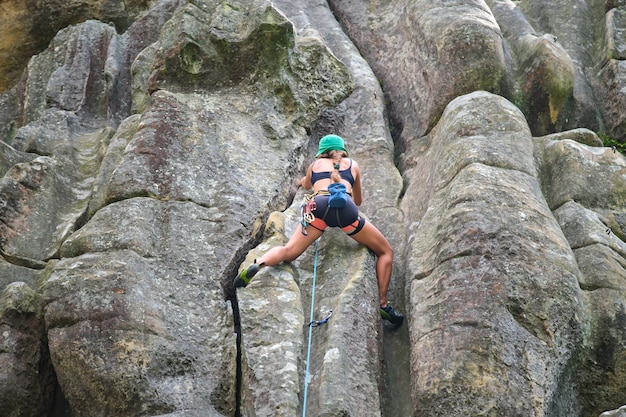 Zdeterminowana dziewczyna wspinacz wspina się po stromej ścianie skalistej góry. sportsmenka pokonująca trudną trasę. zaangażowanie w sporty ekstremalne i koncepcję hobby wspinaczki skałkowej.