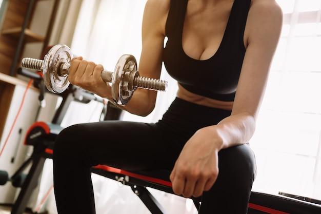 Zdeterminowana kobieta chudnie w domu i ćwiczy z hantlami. koncepcja sportu i rekreacji. piękna kobieta w stroju sportowym