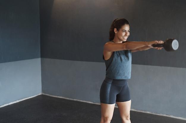 Zdeterminowana, silna latynoska spocona kobieta samotnie trenująca na siłowni z kettlebellem