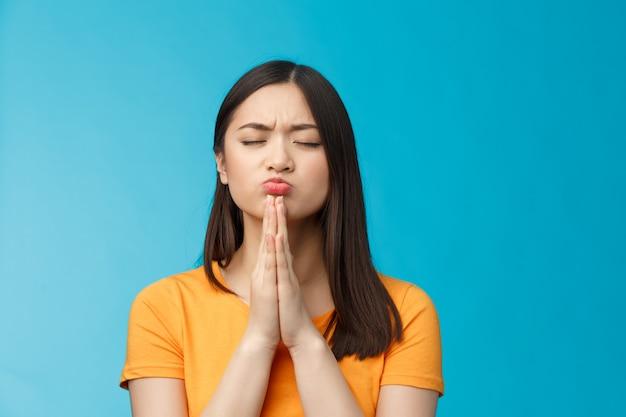 Zdeterminowana, zmotywowana urocza azjatycka kobieta modląca się spełniło się, klepnij ręce razem, módl się w pozie, zamknij oczy dąsając się z chęci wygranej, uzyskaj pozytywną odpowiedź z uniwersytetu, stań na niebieskim tle z nadzieją