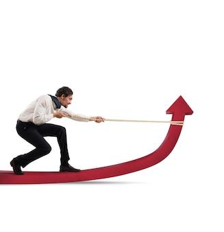 Zdeterminowany biznesmen z dużym wysiłkiem podnosi strzałę statystyki za pomocą liny